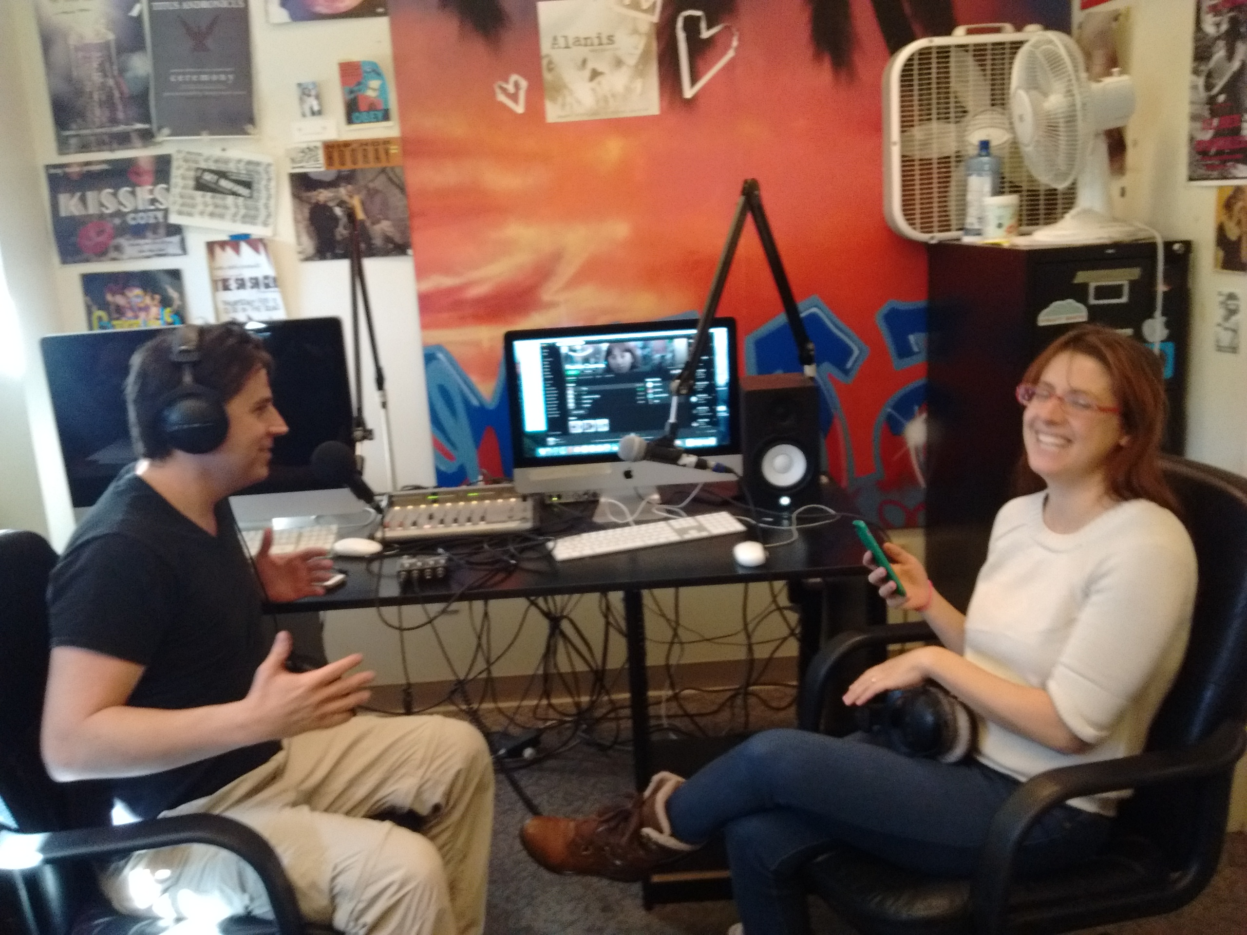 two people in an radio studio laughing